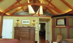 The master suite of this Tidewater style waterfront home was added for the current owner. It includes custom millwork with open timber beams and a diorama of the sea.