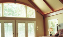 A Master suite with beamed ceiling and expansive water views.