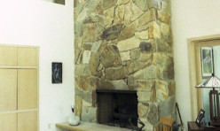 The custom stone fireplace is a feature of this Contemporary waterfront home.