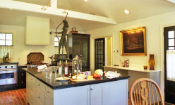 This eat-in Country Kitchen has a vaulted ceiling with custom cable lights above.