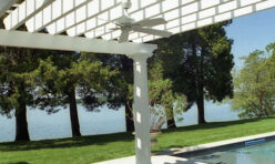 The custom waterfront Pool House Pergola includes a concealed lighting system and a weatherproof fan.
