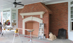 A large design/build addition to an existing waterfront home includes this large porch fireplace.